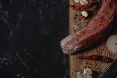 Filetto di carne di maiale crudo fresco sul tagliere di legno su fondo scuro e spazio per il vostro testo fotografia stock