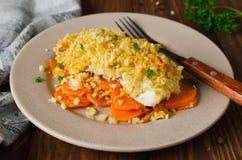 Filetto di pesce arrostito al forno con le carote sotto una crosta del pane immagine stock libera da diritti