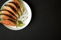 Filetto di pesce di color salmone crudo su fondo nero fotografia stock