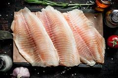 Filetto di pesce su carta su un tagliere fotografia stock