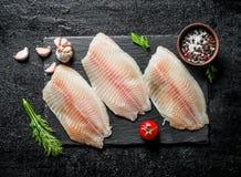 Filetto di pesce sul bordo di pietra nero con aneto, i pomodori e le spezie in ciotola fotografie stock libere da diritti