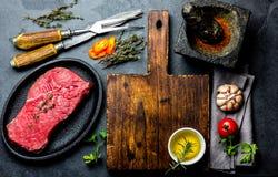 Filetto, erbe e spezie freschi di manzo della bistecca della carne cruda intorno al tagliere Alimento che cucina fondo con lo spa fotografie stock libere da diritti