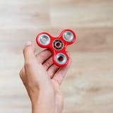 Fileur de personne remuante Fileur rouge de main, jouet remuant de main tournant sur la main du ` s d'enfant Détente Anti adhd AT Photos stock