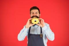 Filhós da posse do padeiro Moderno engraçado Filhós doce Homem do cozinheiro chefe no café Dieta e alimento saudável Dieta da fil fotografia de stock