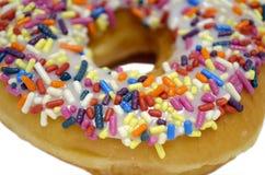 A filhós doce com os doces do arco-íris polvilha em superior isolados no fundo branco imagens de stock royalty free