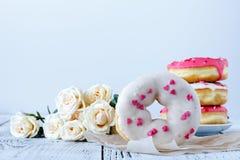 A filhós e o café bonitos da surpresa da manhã e aumentaram Fotos de Stock Royalty Free
