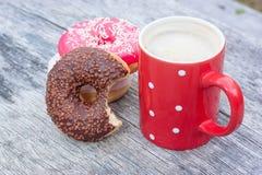 Filhós mordida do chocolate com xícara de café vermelha Imagens de Stock