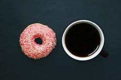 Filhós no esmalte cor-de-rosa e xícara de café no fundo escuro, vista de cima de foto de stock royalty free
