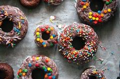 Filhóses cozidas do chocolate com o esmalte e os confeitos que cobrem o Imagens de Stock