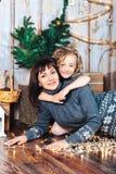 A filha abraça a mamã que encontra-se no assoalho contra o contexto do cenário do ` s do ano novo, luzes de incandescência seguin Imagens de Stock Royalty Free