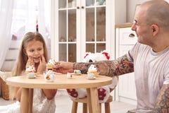 Filha ador?vel que veste um whith branco do vestido seu pai de amor Est?o bebendo o ch? dos pratos de um brinquedo em uma crian?a fotos de stock royalty free