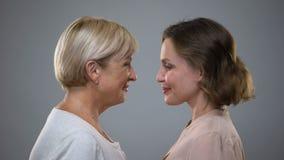 Filha adulta e mãe que tocam nas testas que olham-se, amor da família filme