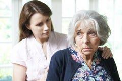 Filha adulta que consola a mãe superior em casa Fotos de Stock Royalty Free