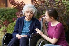 Filha adulta que consola a mãe superior na cadeira de rodas foto de stock