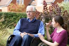 Filha adulta que consola o pai superior In Wheelchair imagens de stock