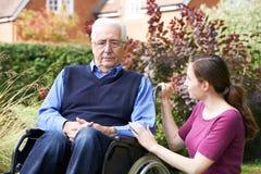 Filha adulta que consola o pai superior In Wheelchair imagem de stock
