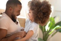 Filha africana bonito da criança que ri agradando o paizinho preto em casa fotografia de stock royalty free
