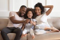 Filha africana e pais que olham o smartphone que ri no sofá imagem de stock royalty free