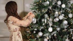 A filha ajuda minha mãe a decorar a árvore, ao lado de seus marido e posses um filho em seus braços video estoque