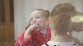 A filha apressa-se nos braços do ` s da mãe em casa e dá-se lhe um abraço grande video estoque