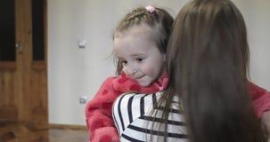 A filha apressa-se nos braços do ` s da mãe em casa e dá-se lhe um abraço grande vídeos de arquivo