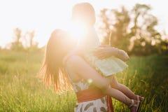 A filha bonita feliz dos beijos e dos abraços da mamã na natureza no por do sol ilumina-se foto de stock royalty free