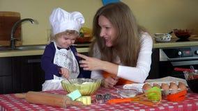 A filha bonito com mãe pôs a farinha sobre o nariz Meninas brincalhão da família na cozinha video estoque