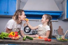 A filha bonito dá a sua mãe uma parte de pimenta búlgara a provar foto de stock royalty free