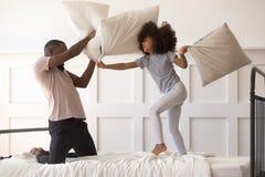 Filha bonito que joga a luta de descanso na cama com paizinho africano imagens de stock