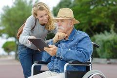 Filha com o pai na cadeira de rodas usando a tabuleta no parque fotos de stock royalty free
