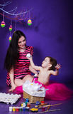 Filha com sua mãe que prepara-se para comemorar a Páscoa Fotografia de Stock Royalty Free