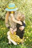A filha dá a mamã aspirar dos dentes-de-leão Imagens de Stock
