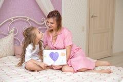 A filha da criança felicita a mamã e dá-lhe um cartão fotos de stock