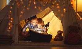 A filha da mãe e da criança com um livro e uma lanterna elétrica antes vai foto de stock