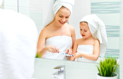 A filha da mãe e da criança escova seus dentes com escova de dentes foto de stock