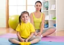 Filha da mãe e da criança que faz a ioga em casa foto de stock