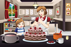 Filha da mãe que decora um bolo Fotos de Stock