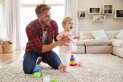Filha de ajuda da criança do pai novo para andar na sala de estar foto de stock royalty free