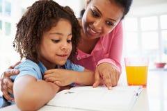 Filha de ajuda da mãe com trabalhos de casa na cozinha fotografia de stock royalty free