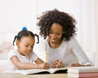 A filha de ajuda da matriz faz trabalhos de casa no manual de instruções Imagens de Stock Royalty Free
