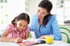 Filha de ajuda da mãe com trabalhos de casa Foto de Stock Royalty Free