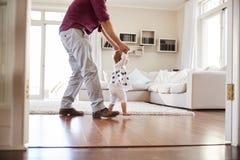 A filha de ajuda do pai aprende andar em casa, vista lateral imagens de stock royalty free