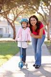 Filha de ensino da mãe para montar o 'trotinette' Imagem de Stock