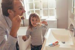 Filha de ensino do pai como escovar os dentes fotos de stock