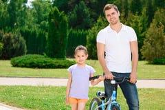 Filha de ensino do pai para montar uma bicicleta Imagem de Stock