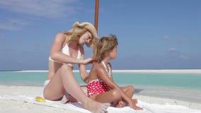 Filha de protecção da mãe com loção de Sun no feriado da praia video estoque