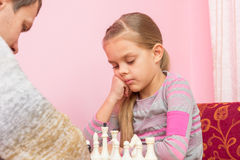 A filha de sete anos está pensando sobre o próximo passo, jogando a xadrez Imagens de Stock Royalty Free