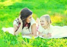 Filha de sorriso feliz da mãe e da criança que encontra-se junto na grama Fotos de Stock Royalty Free
