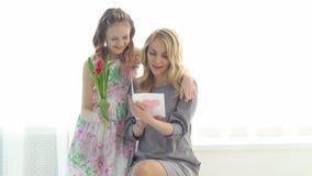 A filha deu a sua mãe um ramalhete das tulipas e um cartão feito com suas próprias mãos Maternidade feliz vídeos de arquivo