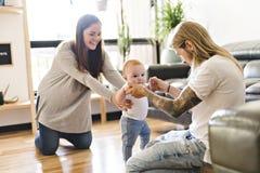 A filha do bebê da ajuda do pai para tomar primeiramente pisa em casa imagens de stock